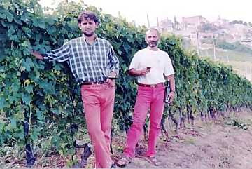 Enzo and Gianni Boglietti brothers in their vineyard. In the back the city of La Morra